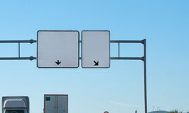 Two blank highway signs overhead. Trucks on road with trucks. Your message here. Copyspace on two roadsigns. Two blank highway signs, each has arrow pointing stock photos