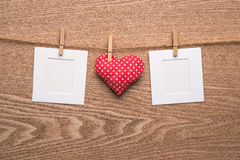 Two blank instant photos with hearts on wooden background. Royalty Free Stock Images