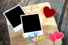 Two blank instant photos with red hearts. On wooden background Stock Photos