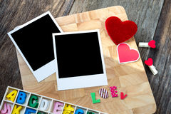 Two blank instant photos with red hearts. On wooden background Royalty Free Stock Photography