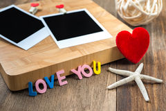 Two blank instant photos with red hearts.On wooden background Stock Photography