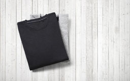 Two blank jumpers lying on white wood background Royalty Free Stock Images