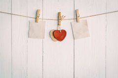 Two blank old paper and red heart hanging. On white wooden Royalty Free Stock Images
