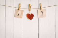 Two blank old paper and red heart hanging. On white wooden Stock Photos