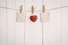 Two blank old paper and red heart hanging. On white wooden Stock Photography