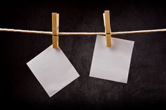 Two Blank paper notes hanging on rope with clothes pins Royalty Free Stock Images