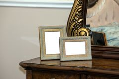 Chest of drawers with two blank photo frames. Two blank photo frame on the chest of drawers. Mock up of blank photo frames Royalty Free Stock Image