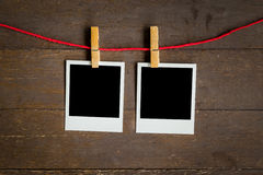 Two blank photo frame hanging on wood background Stock Photo