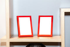 Two blank photo frames on the bookshelf Royalty Free Stock Photos
