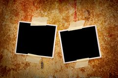 Two blank photographs. Two blank photos on a grungy wooden background Royalty Free Stock Image