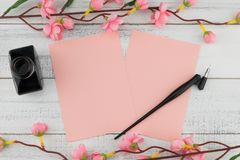 Two blank pink card, oblique pen and bottle of ink. Decorated with fake pink flower branches on white wood background Stock Photos
