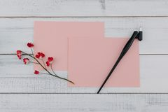 Two blank pink card and oblique pen decorate with red paper flower. S on white wood background Stock Photography