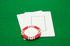 Two blank play cards with casino chip on green Royalty Free Stock Photos