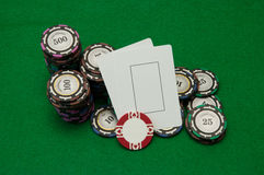 Two blank play cards with stacks of casino chips on green Stock Photo