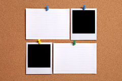 Two blank polaroid style photo prints with index cards on cork notice board, copy space royalty free stock photo