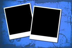 Two blank polaroids. Two blank polaroid style photo frames on a blue grunge illustrated background Royalty Free Stock Photos