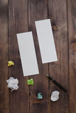 A two blank sheet of paper pen and damaged the paper. Two White clean sheet of paper, a black pen and a broken multi-colored paper on a dark wooden table. the royalty free stock images