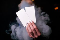two blank white business cards in a woman`s hand stock photos