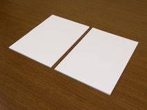 Two blank white papers on a wooden background Royalty Free Stock Images