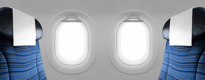 Two blank windows plane with blue seats. In soft light royalty free stock photo