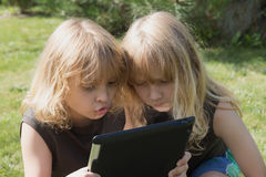 Two blond boys are playing with the tablet outdoors Royalty Free Stock Images