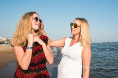 Two blond girls on the beach near sea. Or ocean. Mother and daughter have fun together Stock Images