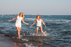Two blond girls on the beach near sea. Or ocean. Mother and daughter have fun together Stock Photography