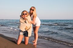 Two blond girls on the beach near sea Stock Images