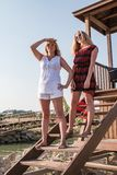Two blond girls on the beach near sea Royalty Free Stock Photos