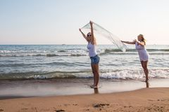 Two blond girls on the beach near sea. Or ocean. Mother and daughter have fun together Stock Image