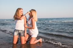 Two blond girls on the beach near sea. Or ocean. Mother and daughter have fun together Stock Photo