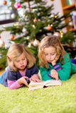 Two blond girls reading a book  in front of christmas tree. Two girls reading a book  in front of christmas tree Stock Image