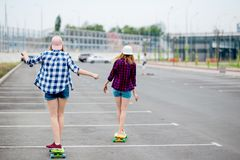 Two blond girls wearing checkered shirts, caps and denim shorts are longboarding on the empty car park. Sport and cool stock images
