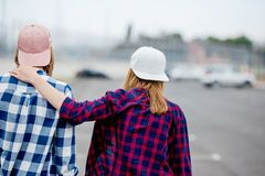 Two blond girls wearing checkered shirts, caps and denim shorts are standing with their backs on the empty car park. Sport and cool style stock images