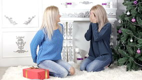 Two blond hair girls exchanging Christmas gifts. Two young, blond hair, women woman, lady, ladies exchanging giving each other Christmas presents, gifts. Smiling stock video