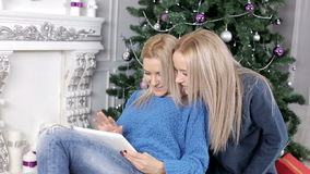 Two blond hair girls watching into the tablet near the Christmas tree stock footage
