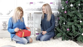 Two blond hair ladies exchanging Christmas presents. Two young, blond hair, women woman, lady, ladies exchanging giving each other Christmas presents, gifts stock video footage