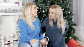 Two blond hair ladies speaking about something siting on the carpet near the Christmas tree stock footage