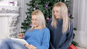 Two blond hair ladies watching into the tablet near the Christmas tree stock video footage