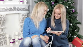 Two blond hair ladies watching into the tablet siting on the carpet near the Christmas tree stock video footage
