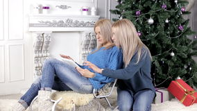 Two blond haired women watching into the tablet near the Christmas tree stock video footage