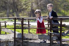 Two blond pretty children, small long-haired girl and cute boy leaning on wooden railings of old bridge looking intently down on w Royalty Free Stock Photography