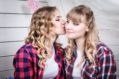 Two blond sisters in the room with white walls. Two blond sisters in the room with white wooden walls Royalty Free Stock Images