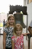 Two blond sisters stand in front of Liberty Bell, at Liberty Bell Center, in front of Independence Hall in historic area of Philad Royalty Free Stock Photos