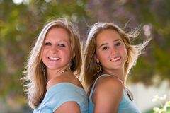 Two Blond Teen Girls Back-To-Back. Two pretty blond teen girls sitting back-to-back with wind-blown hair Royalty Free Stock Photography