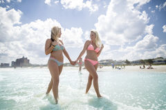 Teenage girls in the sea. Two blond teenage girls in pink and blue bikinis walking hand in hand in the shallow water near the beach, bright blue sky with light Stock Photography