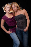 Two blond women. Attractive pair of blond caucasian women standing on black Royalty Free Stock Image