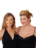 Two Blond Women Smiling in Black Dresses. Two young blond caucasian women in black dresses Royalty Free Stock Photo