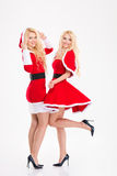 Two blonde beautiful sisters twins in santa claus costumes Stock Photography