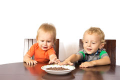 Two blonde brothers eat a race nuts Stock Photo